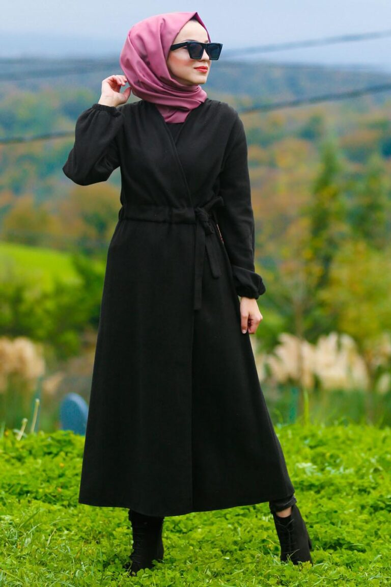 A woman gazing at the nature in style wearing a black trench coat