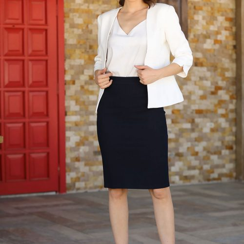 A stylish woman posing wearing a white blazer over a white v-neck top and a black pencil skirt